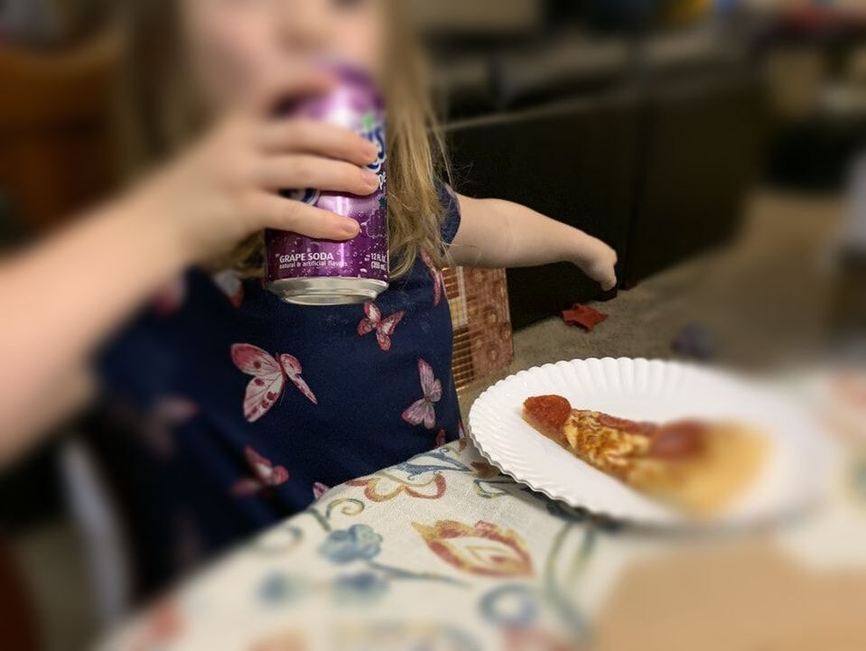 Little girl sitting at the dining room table enjoying a slice of pizza and a soda.